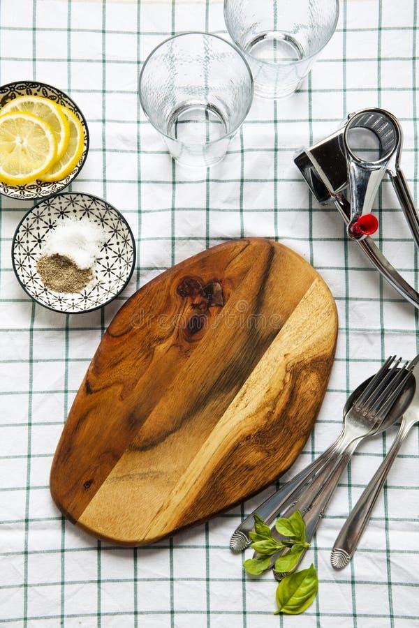 切板,玻璃,乳酪磨丝器,香料 在桌布 库存图片