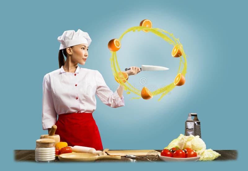 切桔子的亚裔女性厨师 库存照片