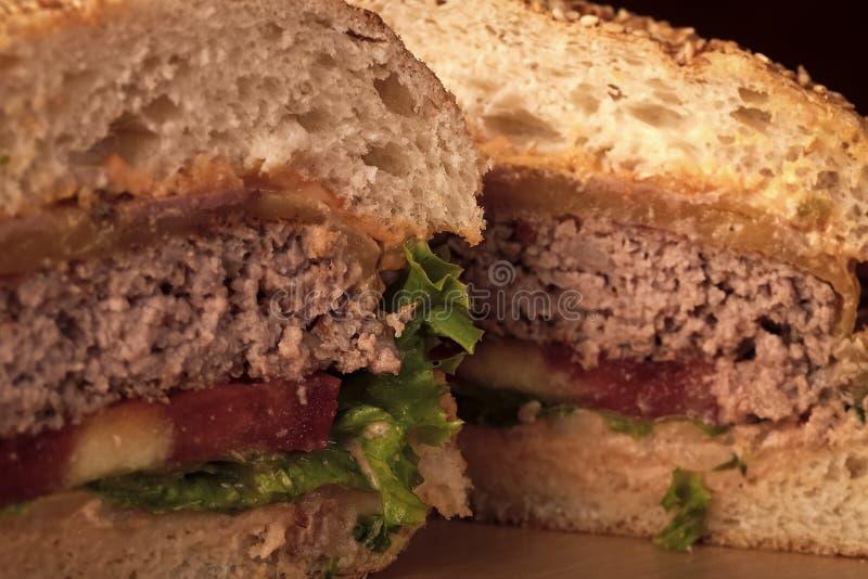 切汉堡 绿色莴苣红色蕃茄乳酪和烟肉切片肉一个大鲜美开胃新鲜的汉堡特写镜头  免版税库存照片