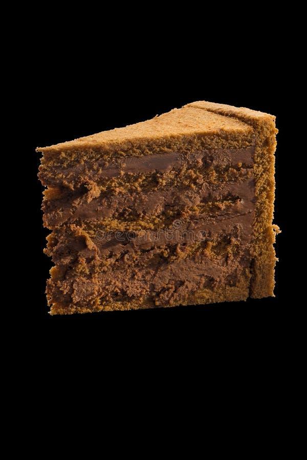 切片与巧克力奶油的巧克力蛋糕在黑ba 免版税库存照片
