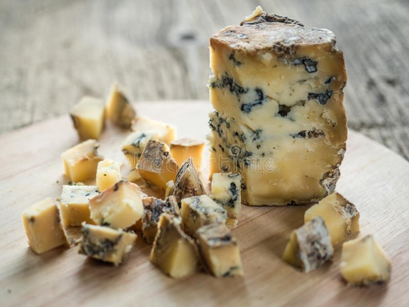 切片与模子的蓝色芬芳英国乳酪Stilton在木背景 r 图库摄影