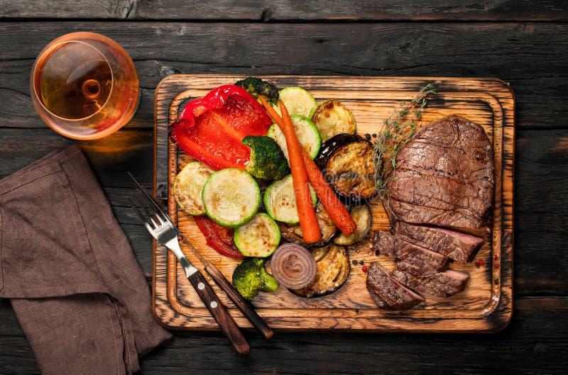 切片与烤菜和白兰地酒的牛排 免版税库存照片