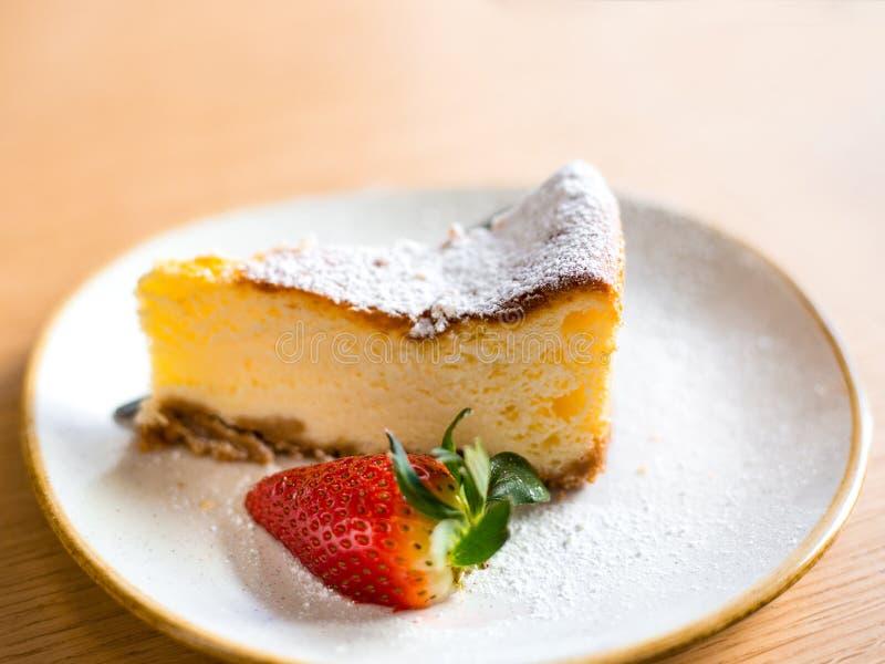 切片乳酪蛋糕用在棕色背景,选择聚焦的草莓 免版税库存照片