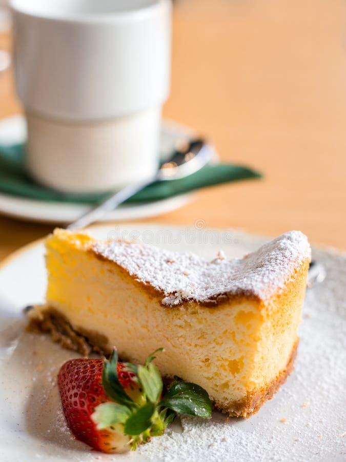 切片乳酪蛋糕用在棕色背景,选择聚焦的草莓 在盘和咖啡的乳酪蛋糕酥皮点心或者 库存照片