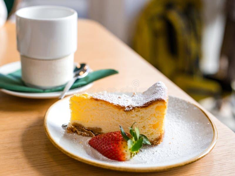 切片乳酪蛋糕用在棕色背景,选择聚焦的草莓 在盘和咖啡的乳酪蛋糕酥皮点心或者 免版税库存照片
