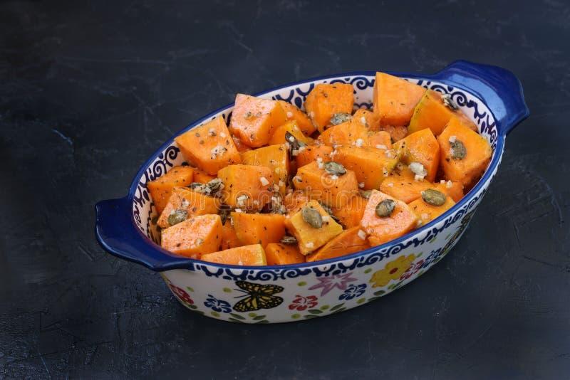切片南瓜用大蒜和种子以一种陶瓷形式在黑暗的背景 免版税库存照片