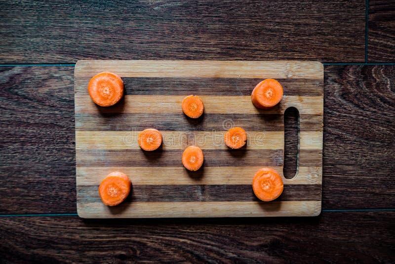 切片在木纹理的红萝卜 免版税库存图片
