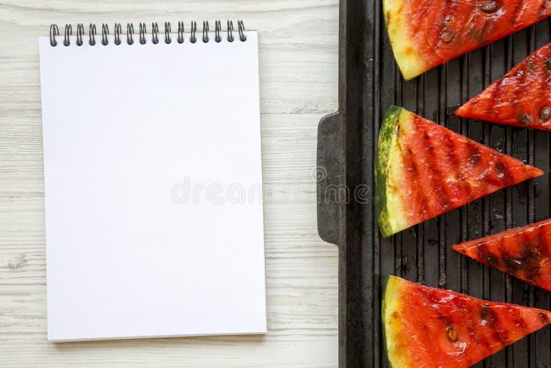 切片在烤平底锅的烤西瓜有在白色木背景的笔记本的,顶视图 免版税库存图片