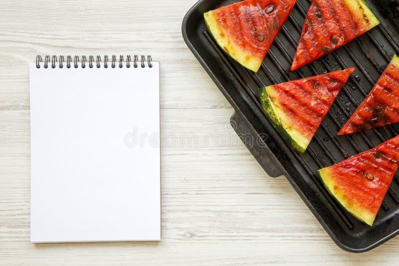 切片在烤平底锅的烤西瓜有白色木表面上的笔记薄的,从上面 库存图片
