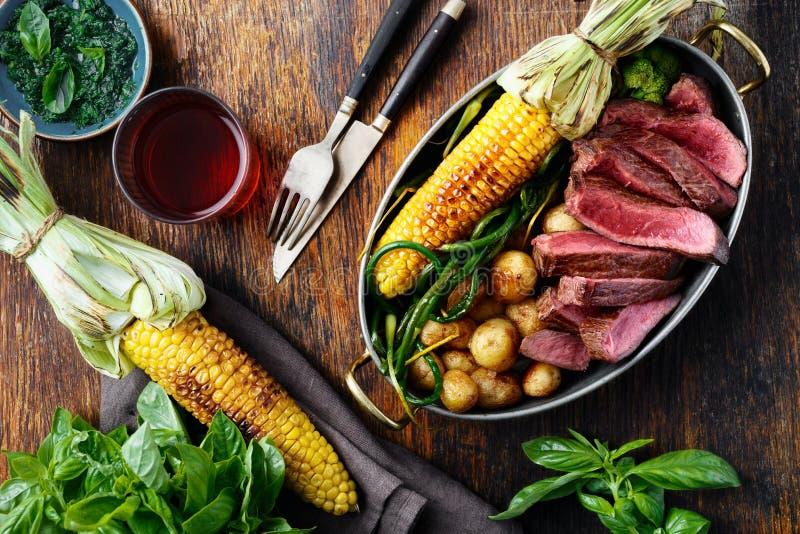 切片在煎锅的牛排有菜和红酒的 免版税库存图片