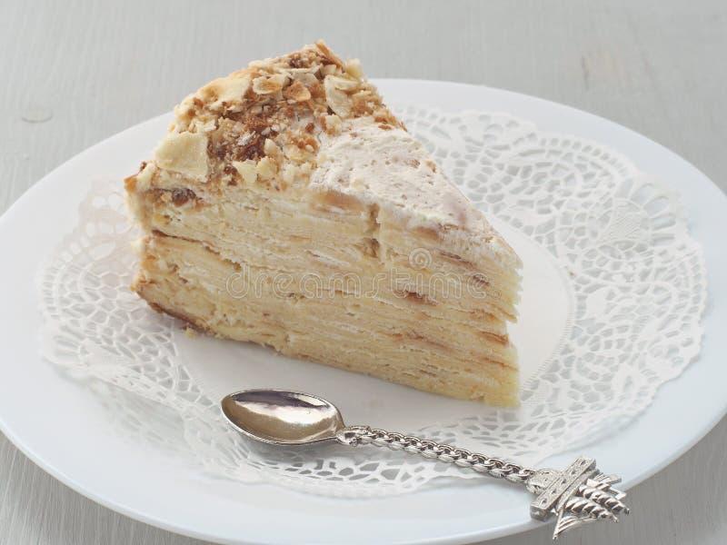 切片在白色板材的mille feuille有在船形状的滑稽的匙子的  多夹心蛋糕 免版税库存图片