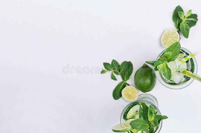切片撒石灰,黄瓜,叶子铸造,冰和透明冷的饮料在白色木板条,顶视图,拷贝空间 免版税库存照片