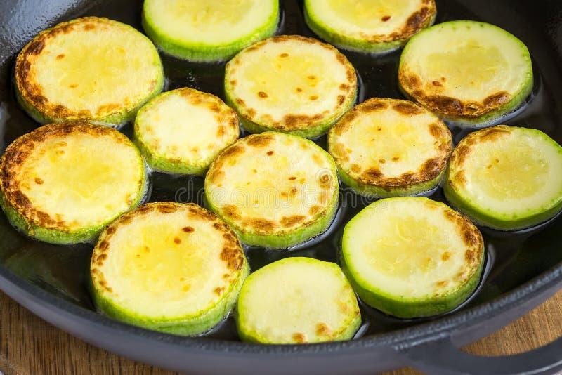 切片新鲜的夏南瓜油煎与在一个大黑生铁平底锅的菜油 : 新鲜的农厂菜和 库存照片