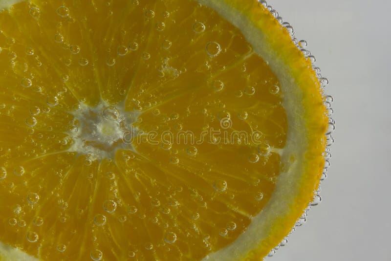 切片新鲜的桔子在水中与泡影 免版税库存图片