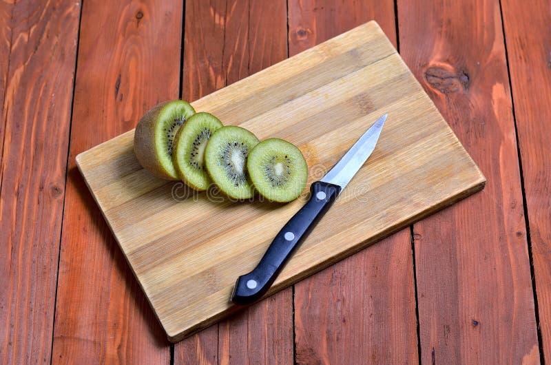 切片新鲜的猕猴桃和一把刀子在木背景 免版税库存图片