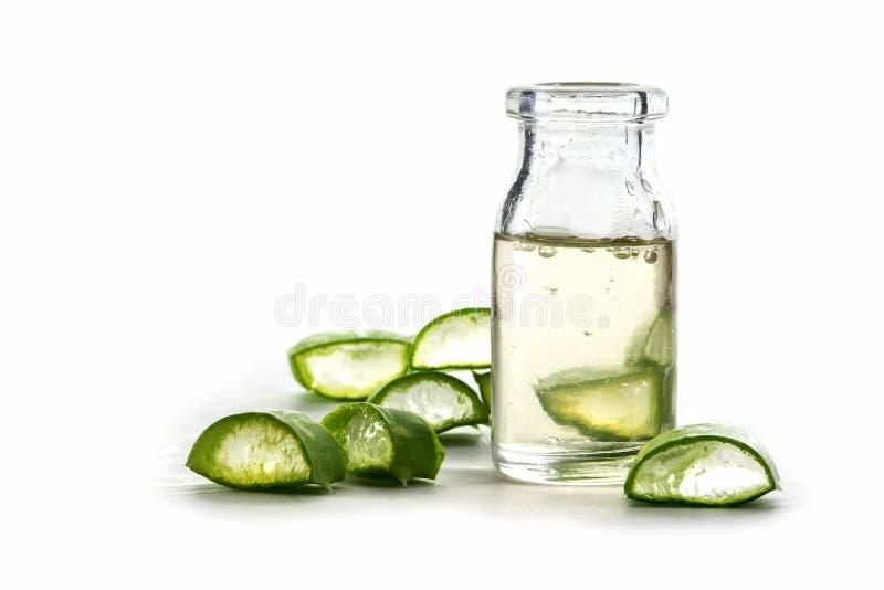 切片新鲜的芦荟维拉叶子和一个瓶有透明的 免版税库存照片