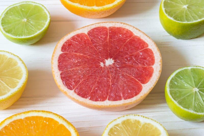 切片柠檬、桔子、石灰和葡萄柚在白色木选项 免版税库存照片