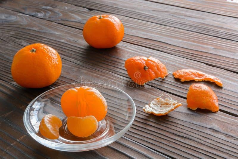切片桔子和一个成熟蜜桔在玻璃茶碟 反对背景老木桌 库存照片