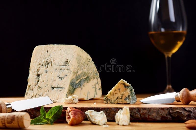 切片法国羊乳干酪乳酪用薄菏 在木板的青纹干酪 库存照片