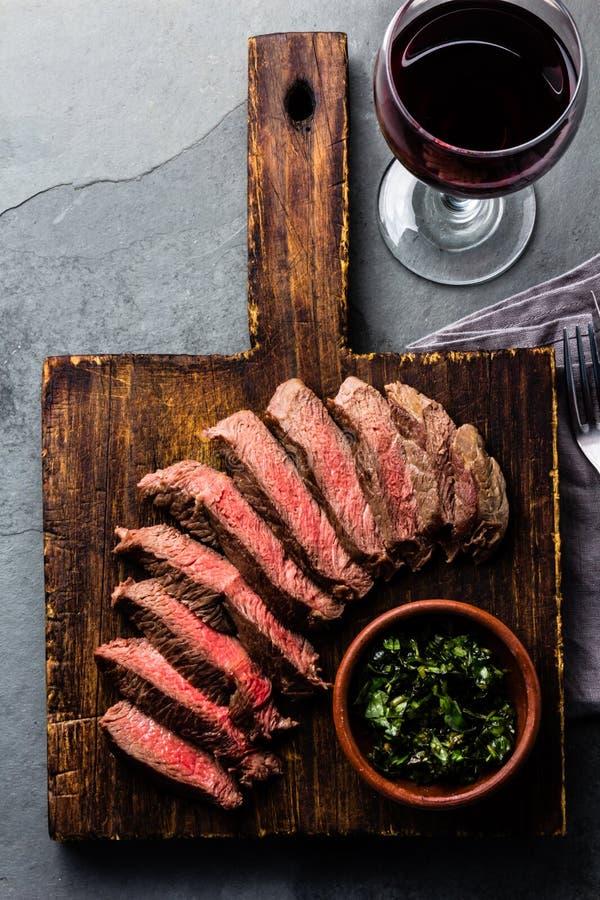 切片牛肉在木板,杯的半生半熟牛排红葡萄酒 免版税库存图片
