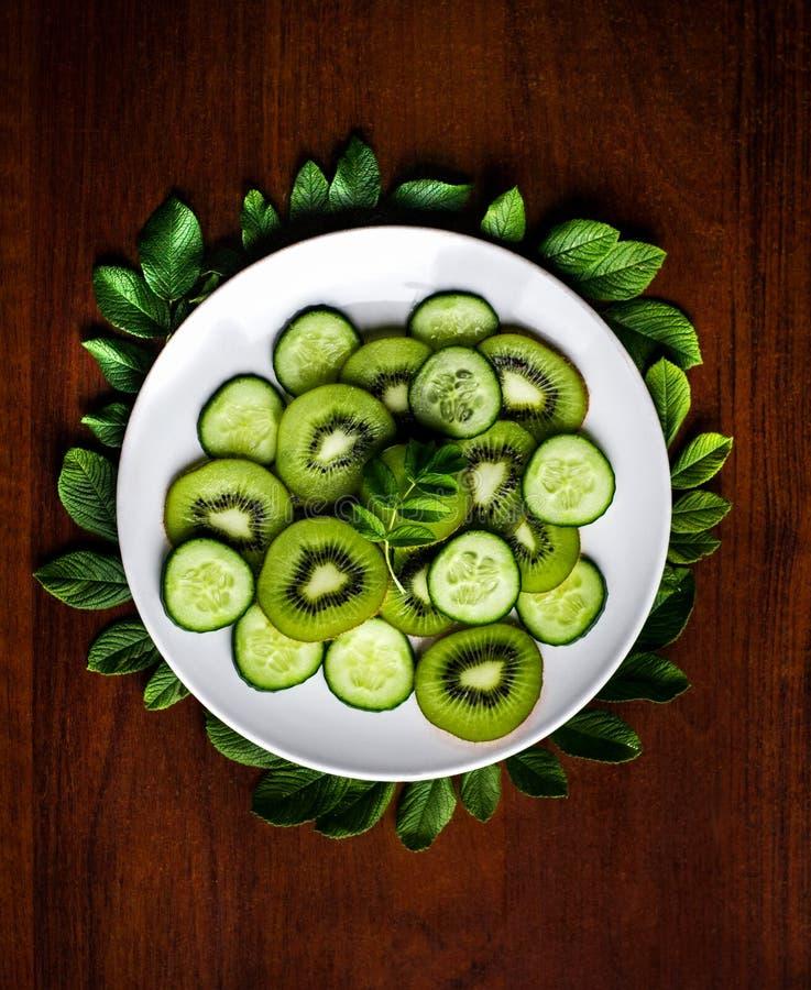 切片猕猴桃和黄瓜与叶子在白色板材和土气backgroun 免版税库存图片
