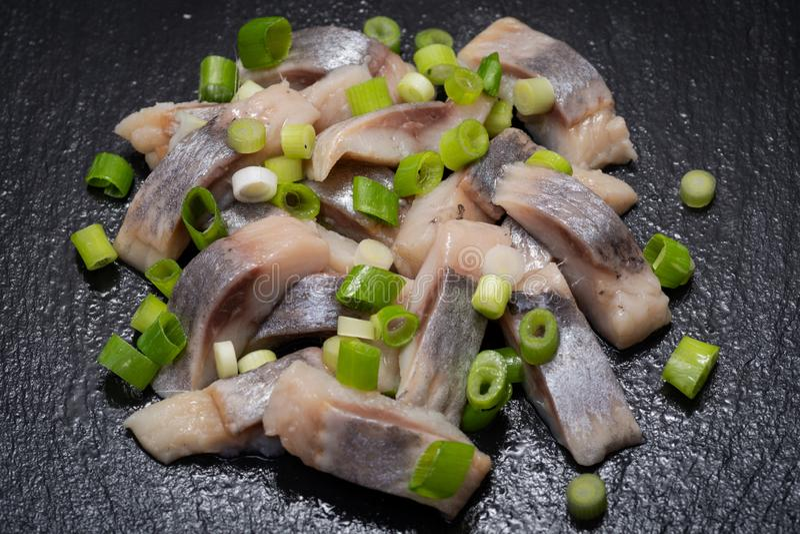 切片盐味的无骨的狂放被捉住的大西洋鲱鱼装饰与切好的大葱薤 黑自然石头 免版税库存图片