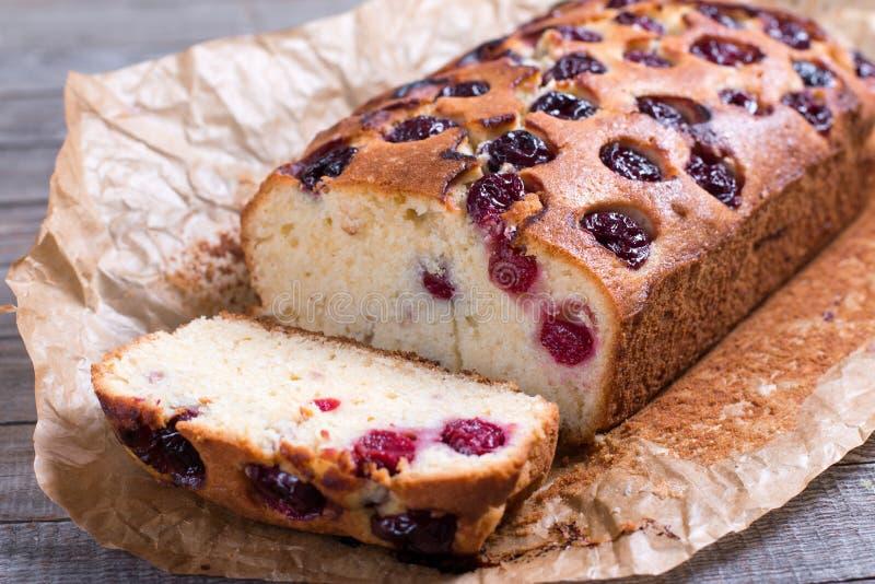 切片自创蔓越桔蛋糕用在木背景的樱桃 免版税图库摄影