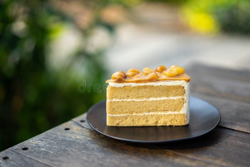 切片自创马卡达姆坚果蛋糕,香草与马卡达姆坚果顶部的夹心蛋糕在一个黑色的盘子在黑暗的木桌w上 图库摄影