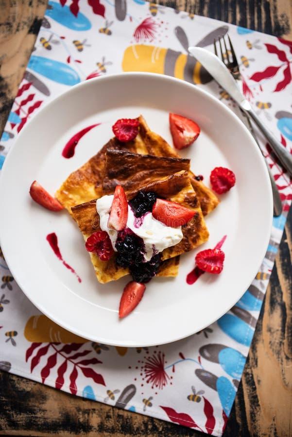 切片芬兰薄煎饼服务与奶油和果子 库存照片