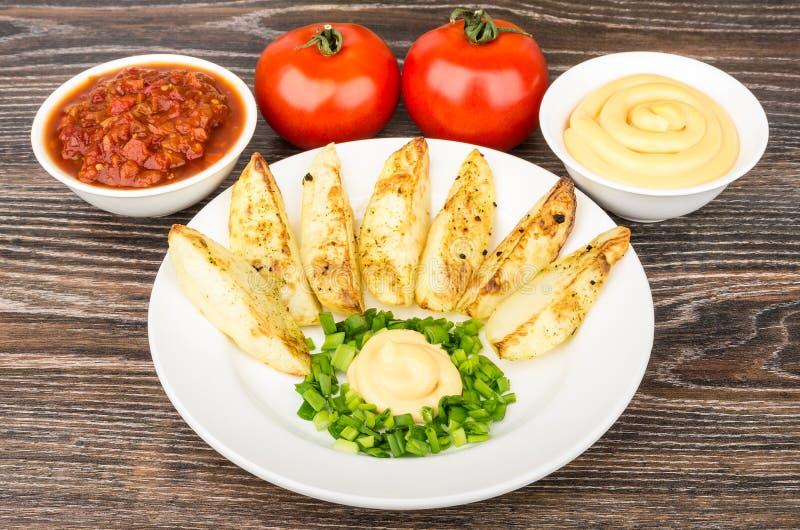 切片被烘烤的土豆用蛋黄酱和韭葱,蕃茄 免版税库存照片