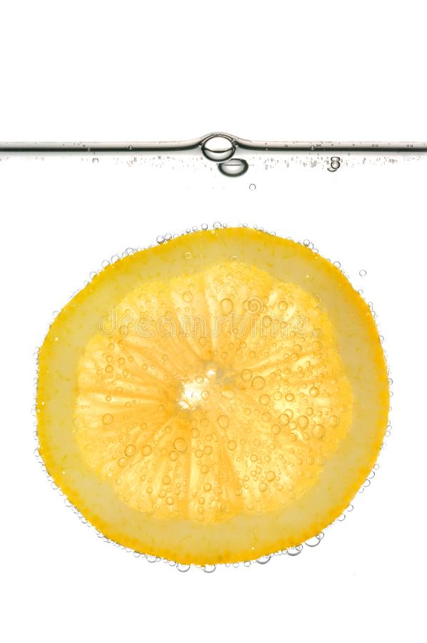 切片黄色柠檬在水中与-被隔绝的泡影 免版税库存照片