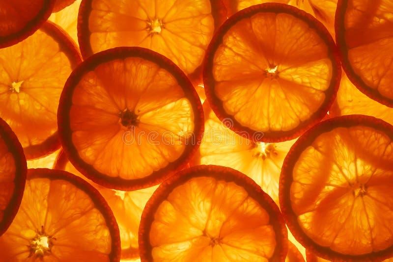 切片黏浆状物质和热心成熟桔子与后照光作为质地背景,基体 整个银幕,特写镜头 库存照片
