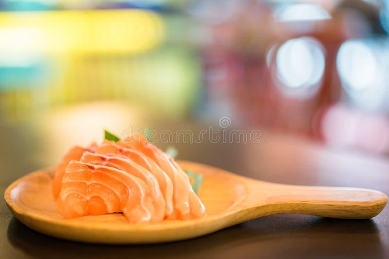 切的三文鱼生鱼片在木盛肉盘,日本食物可口菜单, bokeh服务与拷贝空间的被弄脏的背景 库存照片