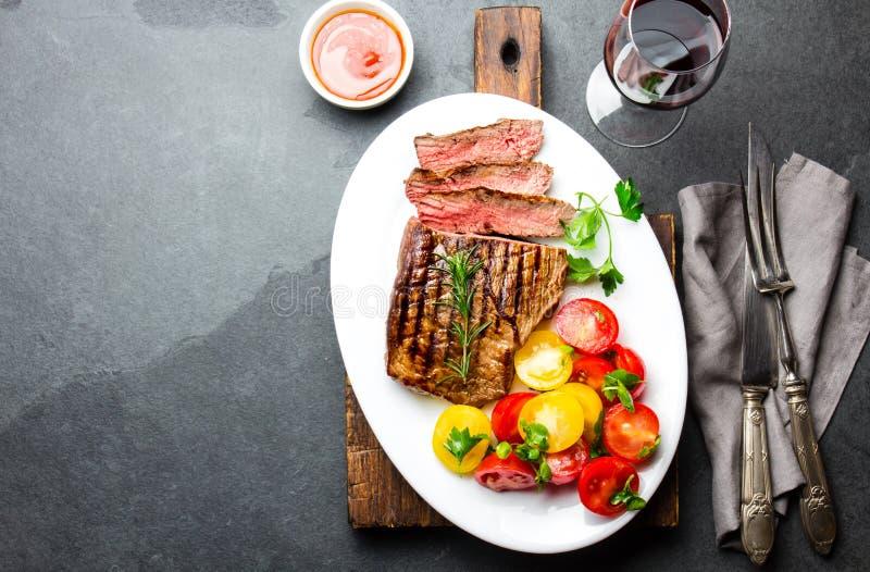 切的半生半熟烤牛排在白色板材服务用蕃茄沙拉和土豆球 烤肉, bbq肉 免版税图库摄影