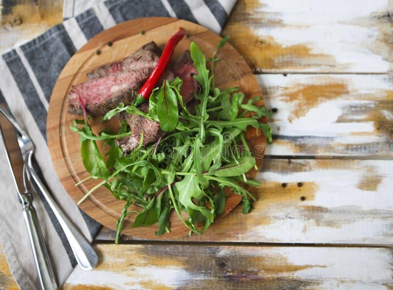 切的半生半熟烤牛排Ribeye用火箭沙拉o 库存图片