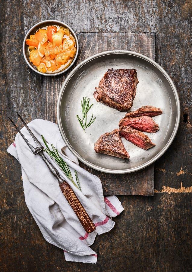 切的半生半熟烤牛肉牛排,小腓厉牛排,在金属土气板材有肉叉子的和辣调味汁调味汁在黑暗的木backgrou 免版税库存图片