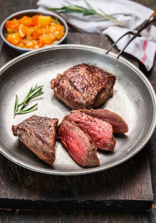切的半生半熟烤牛肉牛排,小腓厉牛排,在金属土气板材有肉叉子的和辣调味汁调味汁在黑暗的木backgrou 库存照片