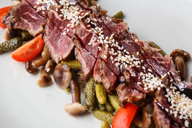 切的半生半熟烤牛肉用腌汁,西红柿,在一块白色板材的蘑菇在木背景 库存图片