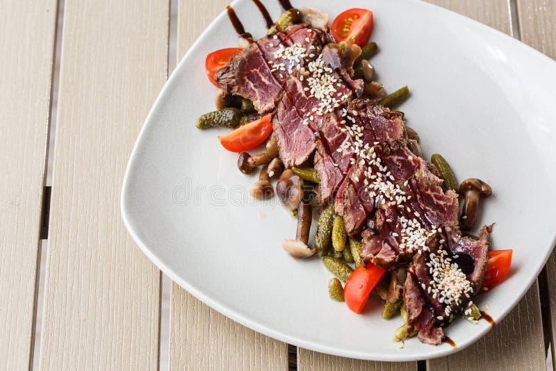 切的半生半熟烤牛肉用腌汁,西红柿,在一块白色板材的蘑菇在木背景 免版税图库摄影