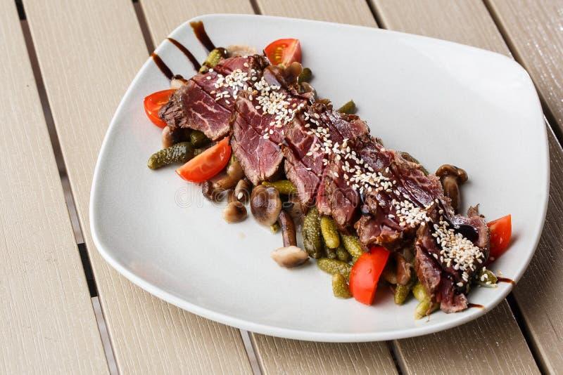 切的半生半熟烤牛肉用腌汁,西红柿,在一块白色板材的蘑菇在木背景 免版税库存照片