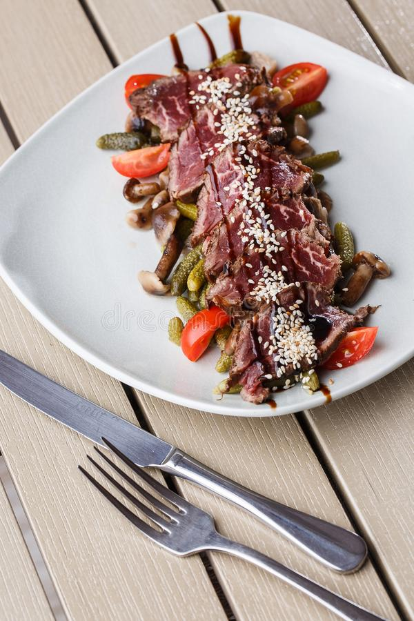 切的半生半熟烤牛肉用腌汁,西红柿,在一块白色板材的蘑菇在木背景 图库摄影