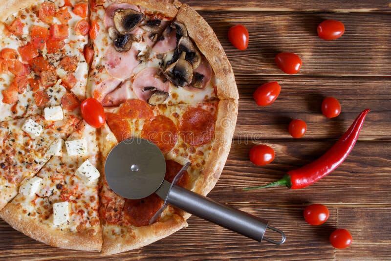 切的四比萨用意大利辣味香肠,蒜味咸腊肠,红辣椒,蘑菇,乳酪,蕃茄,杉木自然木表面上的谎言  库存图片