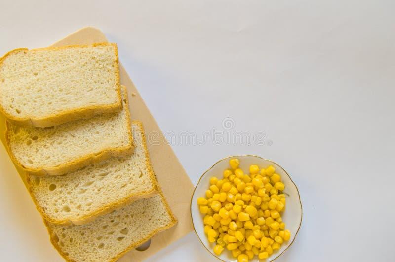 切的新鲜的玉米面面包片断在一个木板和玉米五谷板材的在桌上的 白色被隔绝的背景,顶视图, 免版税图库摄影