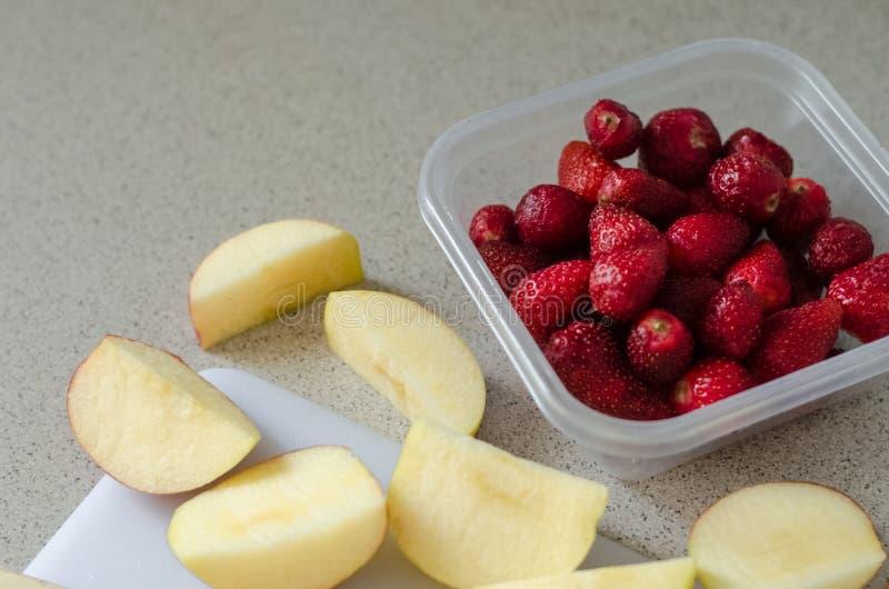 切的新鲜的苹果和草莓在食盒,厨刀在边 库存图片