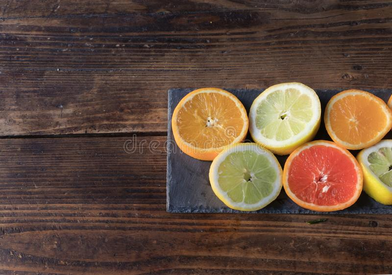 切的柠檬和桔子在板岩板 图库摄影