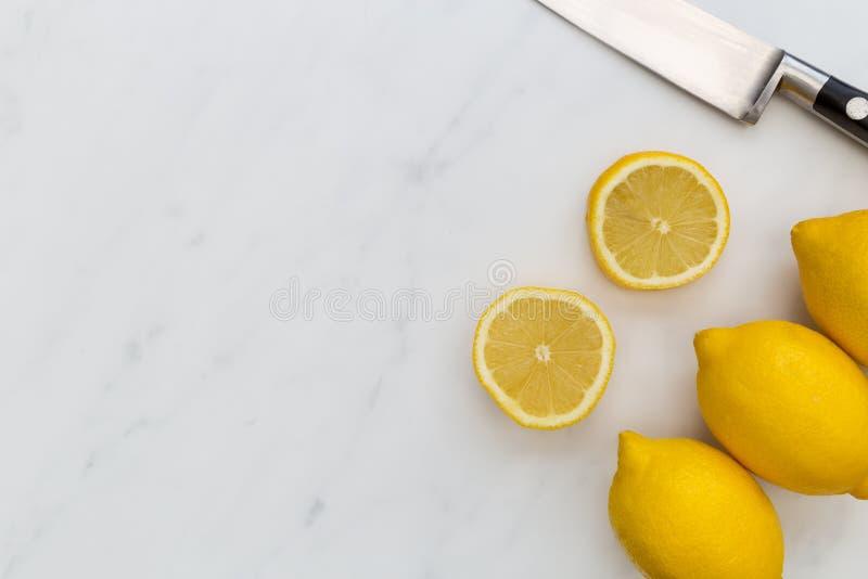切的柠檬果子和刀子在白色大理石背景与co 图库摄影