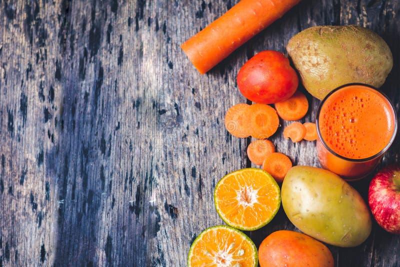 切的桔子、红萝卜、蕃茄、苹果和A杯混合果子a 免版税库存照片
