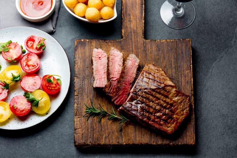 切的烤半生半熟牛排在木板烤肉, bbq肉牛里脊肉服务 顶视图,板岩背景 免版税图库摄影