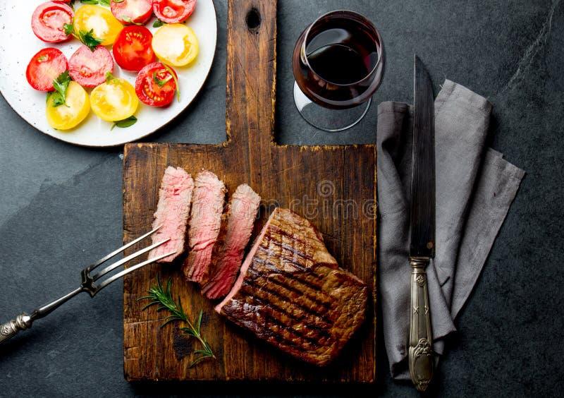 切的烤半生半熟牛排在木板烤肉, bbq肉牛里脊肉服务 顶视图,板岩背景 库存照片