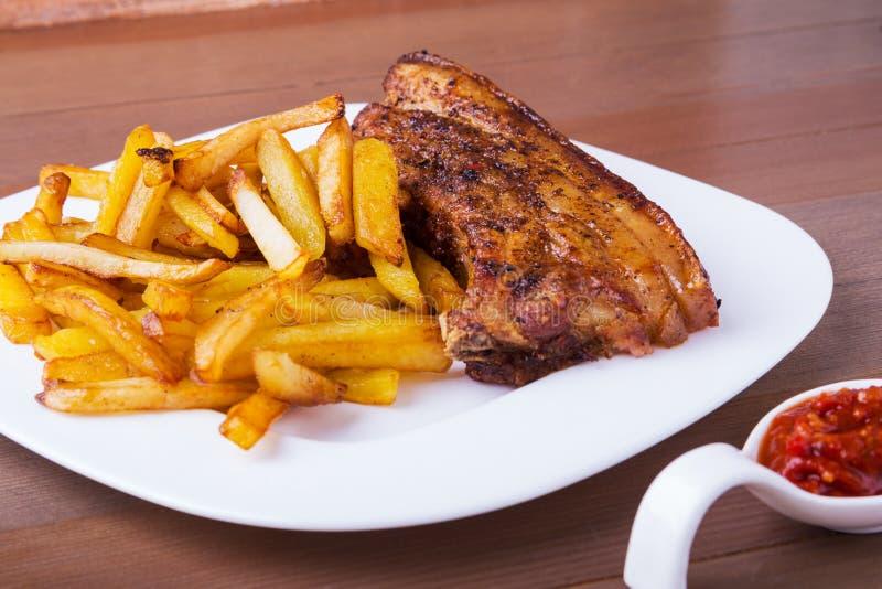 切的烤排骨烤肉Striploin牛排用chimichurri调味汁和土豆免费在白色板材 免版税库存照片